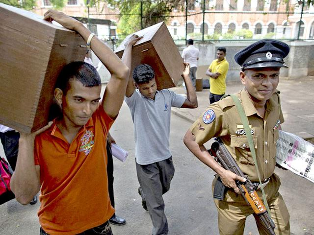 Sri Lankan election workers carry ballot boxes and a police officer carries ballot papers from a polling material distribution center in Colombo a day before the island nation will hold parliamentary elections on August 17, 2015. (AP/PTI photo)