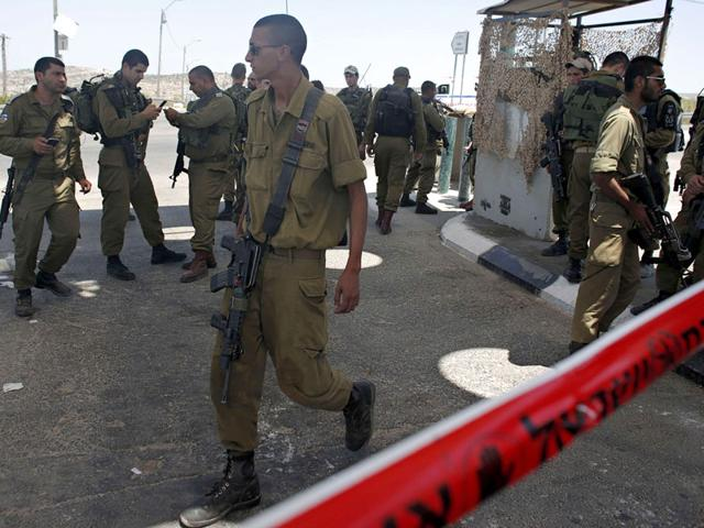 Israeli security forces stand in a security perimeter at the site of an earlier shooting where a Palestinian young man was shot and wounded by Israeli troops after he had stabbed a soldier near West Bank village of Beit Ur, west of Ramallah. (AFP Photo)
