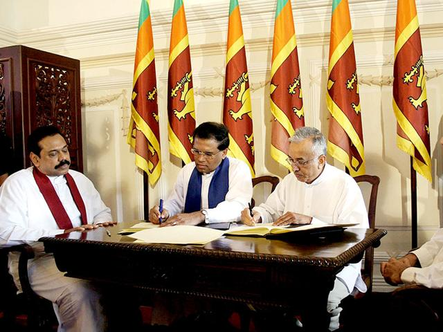 In this photograph taken on October 23, 2006, then Sri Lanka Freedom Party secretary, Maithripala Sirisena (second left) and opposition United National Party senior party official, Malik Samarawickrema (second right) sign an agreement to work together towards a political settlement to the island's drawn out separatist conflict with the rebel Liberation Tigers of Tamil Eelam (LTTE) as the then Sri Lankan President Mahinda Rajapakse (left) of the Sri Lanka Freedom Party (SLFP) looks on in Colombo. (AFP file photo/Lakruwan Wanniarachchi)