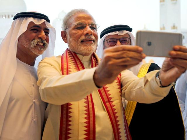 Indian Prime Minister Narendra Modi, middle, takes a selfie next to Sheikh Hamdan bin Mubarak Al Nahyan, UAE Minister of Higher Education and Scientific Research, left, as they tour the Sheikh Zayed Grand Mosque during the first day of his two-day visit to the UAE, in Abu Dhabi, United Arab Emirates, Sunday, Aug. 16, 2015. (AP Photo)