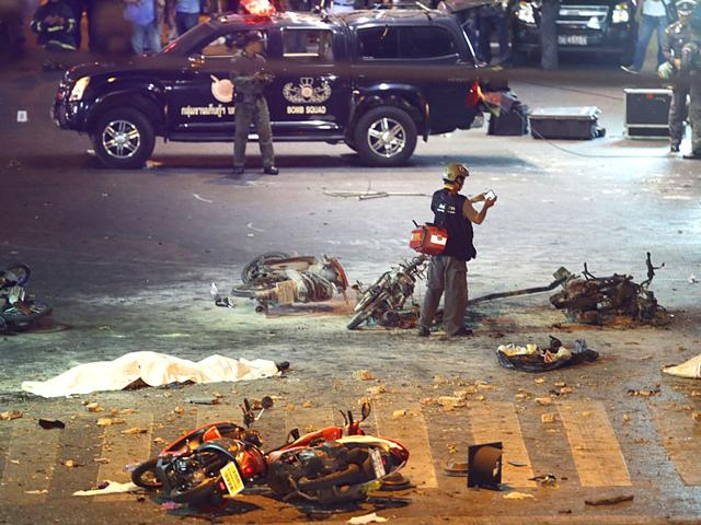 A policeman photographs debris from an explosion in central Bangkok in Thailand on Monday. The large explosion rocked a central Bangkok intersection during the evening rush hour, killing at least three people and injuring 25 others, police said. (AP Photo/Mark Baker)