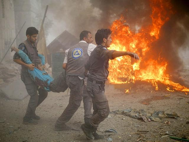 Syrian emergency personnel carry a wounded man following air strikes by Syrian government forces on a marketplace in the rebel-held area of Douma, east of the capital Damascus on August 16, 2015. Over 100 people were killed and 250 people were injured, most of them civilians, the Syrian Observatory for Human Rights said. (AFP Photo/Sameer al Doumy)