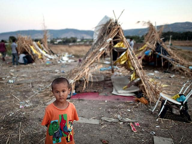 A child stands in front of makeshift shelters outside the abandoned Captain Elias hotel on the Greek Aegean island of Kos (AFP Photo)