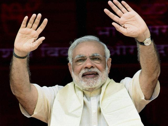 Prime Minister Narendra Modi waves during laying of the foundation stone of four-lane Patna-Buxar road and a bridge parallel to the Abdul Bari bridge over river Sone at Koilwar near Ara on Tuesday. (PTI Photo)