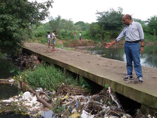 A man points to the sewerage and solid waste in the Shahpura lake in Bhopal. (HT photo)