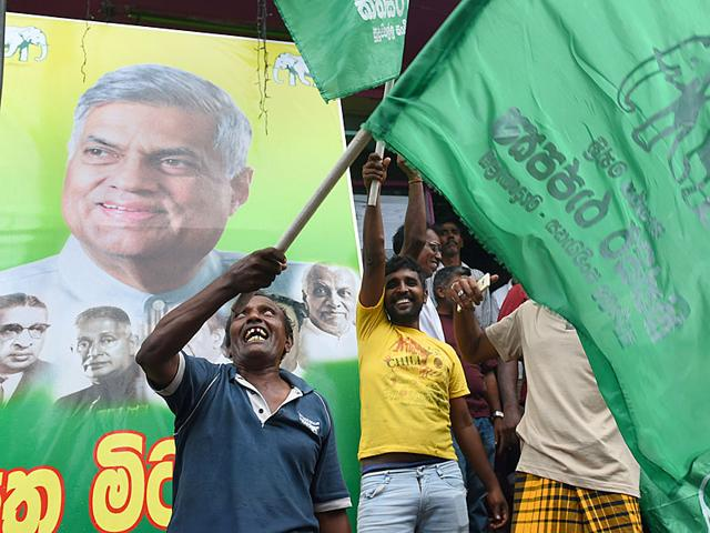 Supporters of Sri Lanka's Prime Minister Ranil Wickremesinghe shout slogans following the general election, in the capital Colombo on August 18, 2015. Sri Lanka's former strongman Mahinda Rajapakse admitted his dream of a political comeback was over, conceding defeat in parliamentary elections while his victorious rival appealed for unity. (AFP PHOTO)