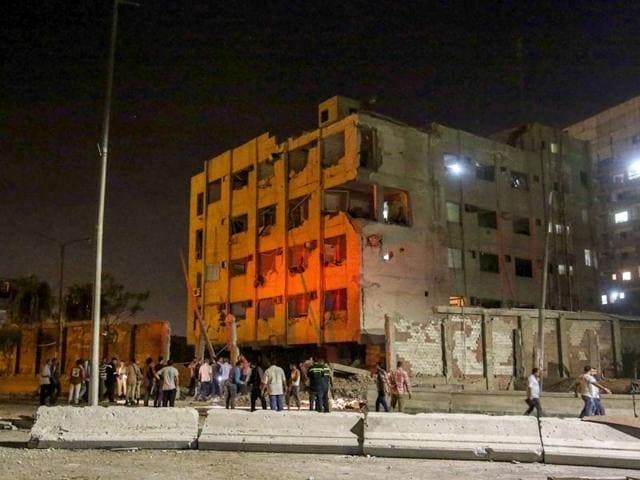 People gather outside an Egyptian national security building after a bomb exploded early on Thursday in the Shubra el-Kheima neighborhood of Cairo, injuring several people including Egyptian security officials. (AP Photo)
