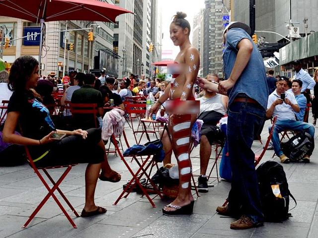 A young woman has her body painted in preparation for posing for photos with tourists in Times Square. (AFP Photo)