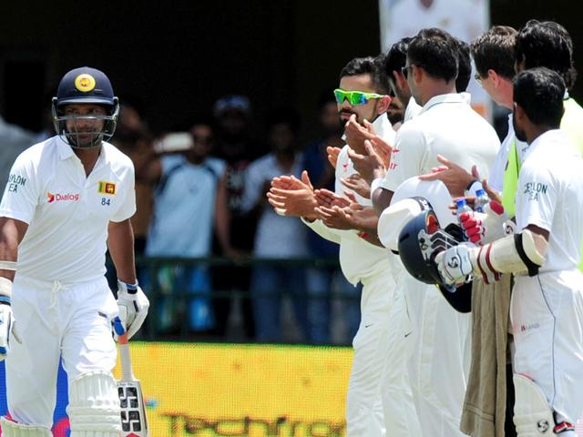 Sri Lankan cricketer Kumar Sangakkara (L) is congratulated by Indian cricket captain Virat Kohli and teammates as he arrives to bat during the second day of the second test match between Sri Lanka and India at the P Sara Oval Cricket Stadium in Colombo. (AFP Photo)