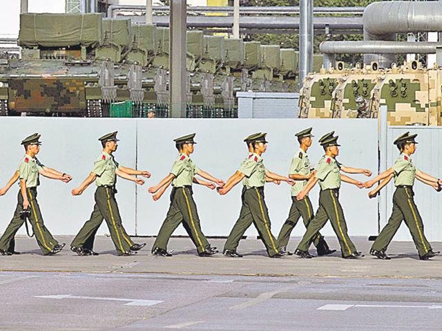 Chinese paramilitary policemen march past military vehicles waiting to take part in rehearsals for the military parade. (AP Photo)