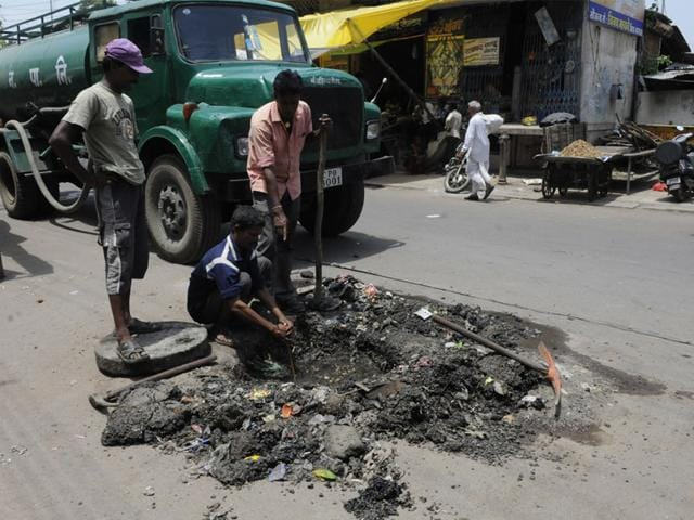 Sanitary workers clear a choked drainage chamber in Nandlalpura area in Indore. (HT file photo)