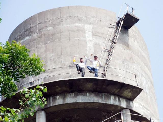 Unemployed linemen with petrol bottles over a water tank at Dhudike village in Moga district on Saturday. (HT Photo)