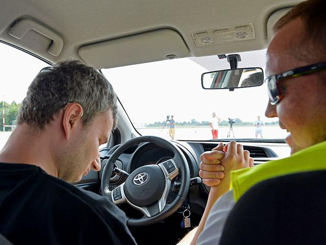 Driving instructor (R) congratulates his contestant (L) during the first TPG Deafblind Race at the airport in Lodz, central Poland. (AFP Photo)