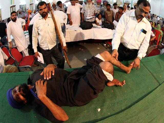 Dr Prabhashankar examinesh a physically handicapped patient during a special campu organised in Ludhiana. (Gurpreet Singh/HT Photo)