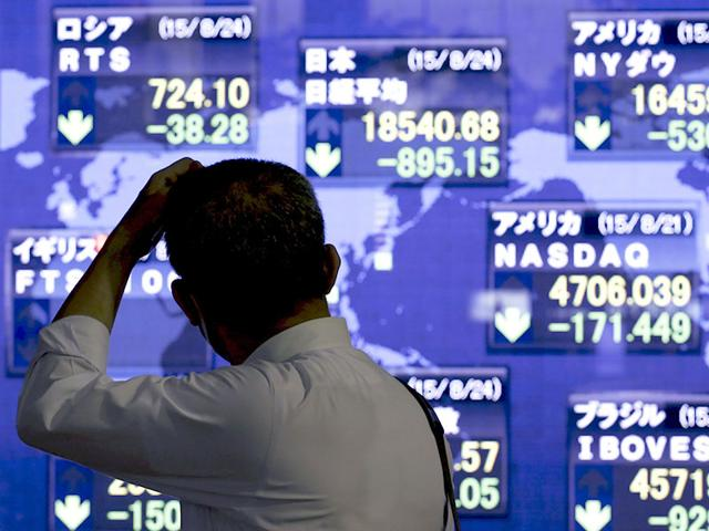 A man looks at market indices at a stock quotation board outside a brokerage in Tokyo, August 24, 2015. Alarm bells rang across world markets on Monday as a 9% dive in Chinese shares and a sharp drop in the dollar and major commodities panicked investors (REUTERS Photo)