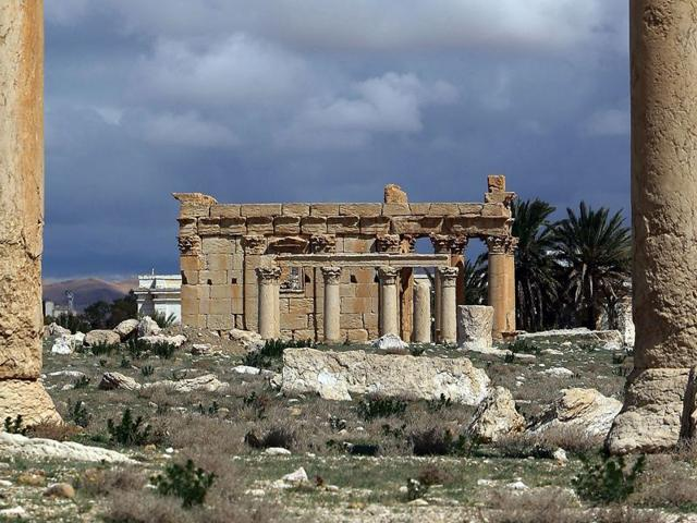 A picture taken on March 14, 2014 shows the Temple of Baal Shamin seen through two Corinthian columns in the ancient oasis city of Palmyra, 215 kilometres northeast of Damascus. Islamic State group jihadists blew up the ancient temple of Baal Shamin in the UNESCO-listed Syrian city of Palmyra, on August 23, 2015 (AFP Photo/Joseph Eid)