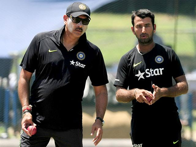 Indian cricket coach Ravi Shastri (L) and Cheteshwar Pujara (R) talk during a practice session at the P Sara Oval Cricket Stadium in Colombo. (AFP Photo)