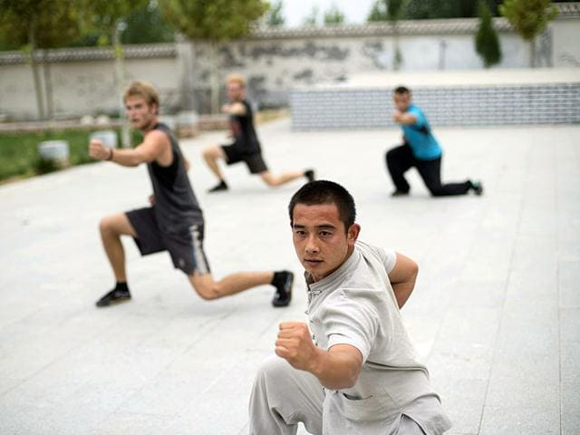 A kung fu master (right) posing with his students at the kung fu academy in Qufu, Shandong province. (AFP)