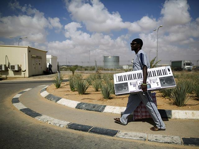 An African migrant carries belongings after being released from Holot detention centre in Israel's southern Negev desert. (Reuters Photo)