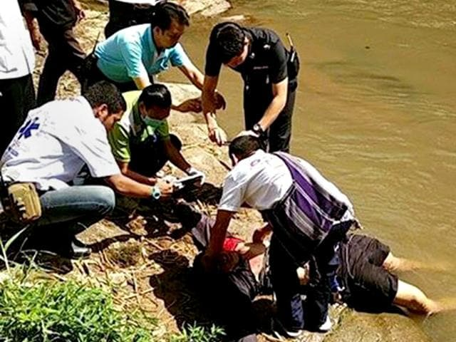 Thai policemen attend to the body of a