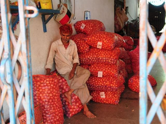 A trader guards his stock of onions at Navbahar vegetable market in Bhopal on Tuesday. (Mujeeb Faruqui/HT photo)
