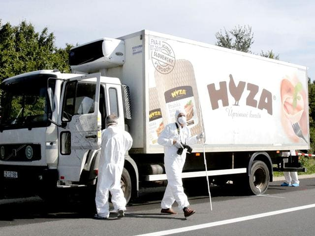 Forensic police officers inspect a parked truck in which up to 50 migrants were found dead, on a motorway near Parndorf, Austria. Police made the grisly discovery in the 7.5-tonne lorry stopped on the A4 motorway near the town of Parndorf, apparently since Wednesday. Police could not put an exact figure on the number of victims, whose bodies had begun to decompose. (Reuters Photo)