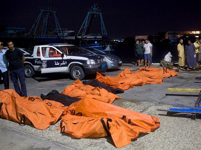 Bodies of migrants who drowned off the coast when their boat sank are collected in Zuwara, Libya. It was not clear how many migrants had drowned. Dozens of boats are launched from lawless Libya each week, with Italy and Greece bearing the brunt of the surge. (AP Photo/Mohamed Ben Khalifa)