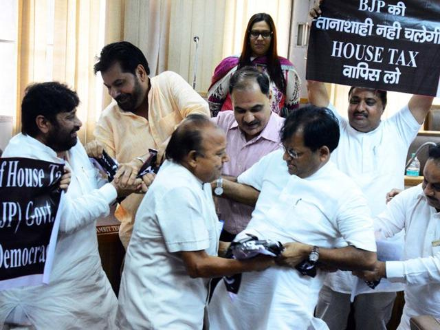 BJP councillors trying to snatch banners from Congress councillors during the MC House meeting in Chandigarh on Thursday. (Sanjeev Sharma/HT)