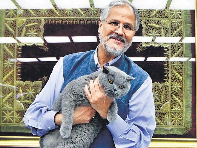 Lieutenant-Governor Najeeb Jung with his cat Munna at Raj Niwas. Jung, who spent a considerable period of his life in Daryaganj, recalls riding through Old Delhi's lanes on his motorcycle, drinking water off the tap and playing football with his milkman. Behind Jung is a masnad (carpet) given to his family by the Mughals (Sanjeev Verma/HT Photo)