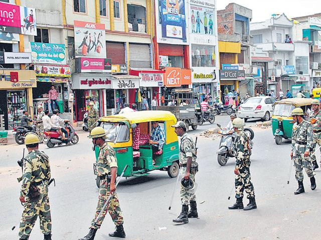 CRPF troopers march in market areas as life returns to normalcy in in Ahmedabad. (PTI Photo)