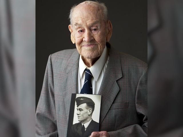 Paul Royle poses for a photo holding a picture of himself in uniform during World War ll, in Perth, Australia. (AP Photo)