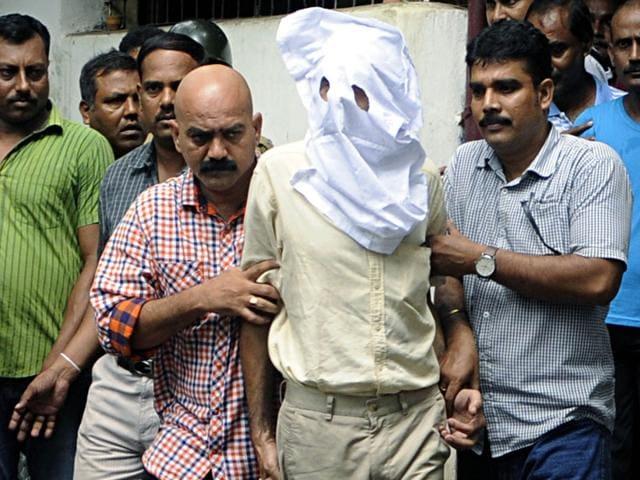 Sanjeev Khanna, face covered, a Kolkata-based businessman being taken to a court on Thursday. (Subhendu Ghosh/HT Photo)