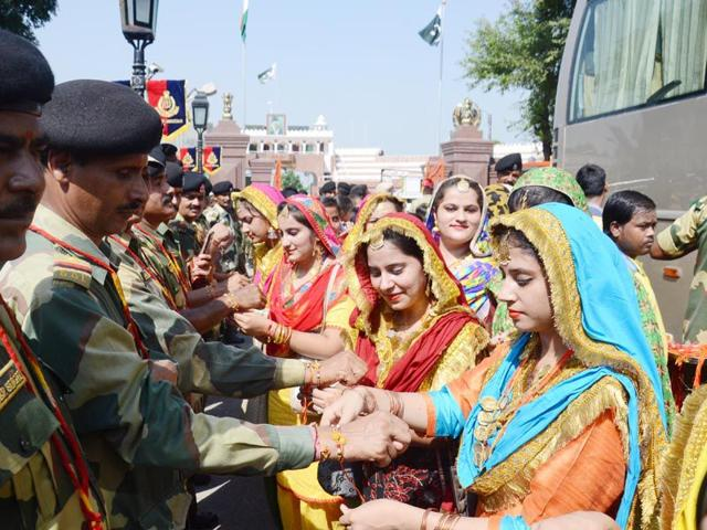 Girls tying rakhis on the wrists of Border Security Force (BSF) jawans on the occasion of Raksha Bandhan at Wagah border in Amritsar on Saturday. Sameer Sehgal/HT