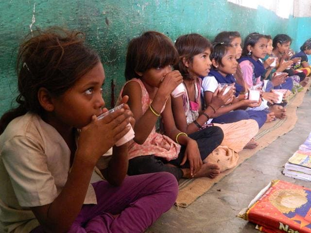 Children drink milk from plastic glasses in Jhabua. (HT photo)