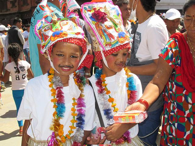 Two young boys dressed in traditional costumes receive eatables from residents as part of Gai Jatra festival in Kathmandu on Sunday. (Utpal Parashar/HT Photo)