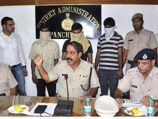 DCP Anil Kumar Dhawan (centre) addressing a press conference after the arrest of the accused (with faces covered) at the mini-secretariat in Panchkula.