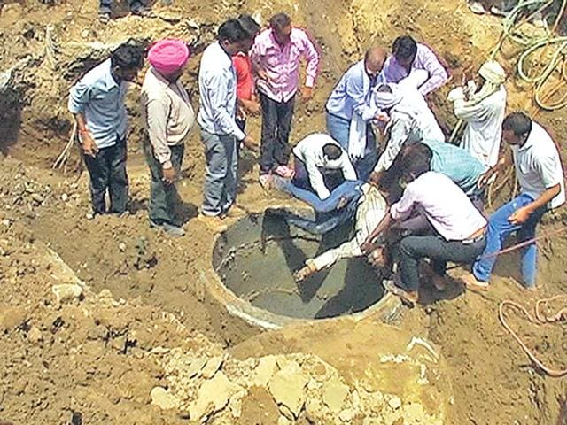People retrieve the bodies of labourers, who fell into in a 20-foot deep sewer near Kali Mori Phatak in Alwar on Monday. (HT Photo)