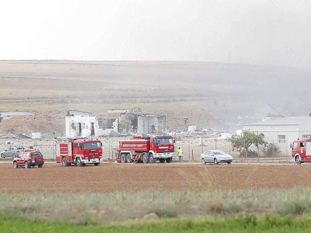 The destroyed fireworks factory Pirotecnia Zaragozana's building is seen behind firefighters trucks after a huge explosion occurred. (AP Photo)