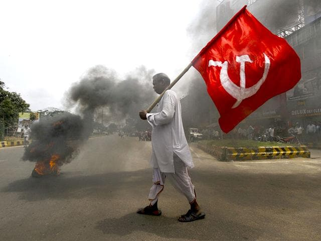 An activist of a trade union group holds a party flag as he walks past a burning tyre during a daylong nationwide strike in Odisha's capital city - Bhubaneswar. (AP Photo/Biswaranjan Rout)