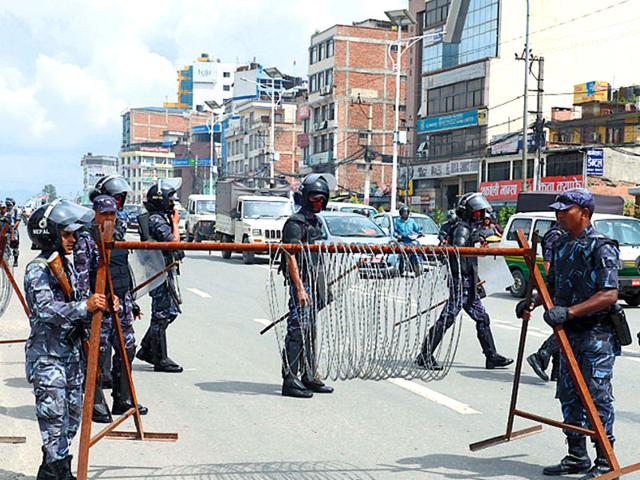 Police personnel block a road in Nepal. Nepal confiscated India-bound Dabur stocks and the company has been facing problems in production and export to India due to the blockade at major border points by Madhesis protesting against Nepal's new constitution since September.