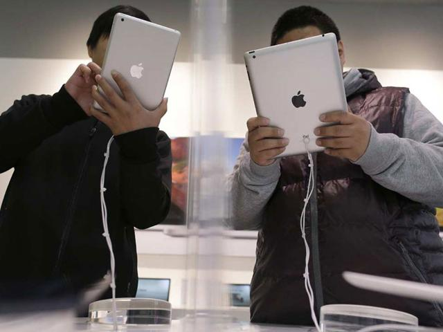 A sales assistant (L) holds an iPad mini next to a customer holding an iPad during the China launch of the iPad mini, in Wuhan, Hubei province. Reuters/Stringer