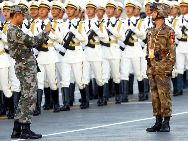A soldier of the People's Liberation Army (PLA) of China has his picture taken as others march in formation past the Tiananmen Square before the military parade. (Reuters Photo)