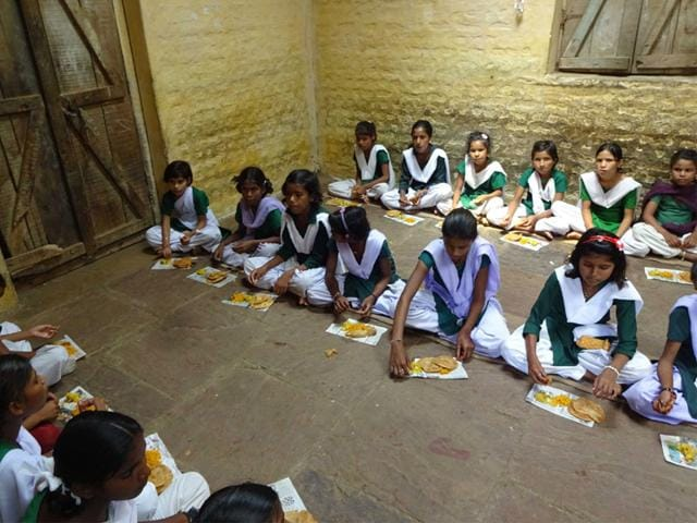 Students of Government Middle School at Parsouriya village in Sagar eating their mid-day meal on pieces of papers. (HT photo)