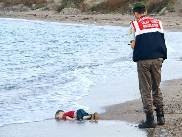 A Turkish gendarmerie stands next to a young migrant, who drowned in a failed attempt to sail to the Greek island of Kos, as he lies on the shore in the coastal town of Bodrum, Turkey. (Reuters Photo)