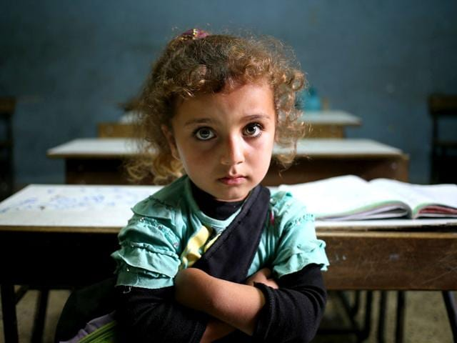 A Syrian refugee girl sits in a classroom at a Lebanese public school where only Syrian students attend classes in the afternoon. 40% of children from five conflict-scarred Middle Eastern countries are not in school warning of a lost generation and a dim future for the region. (AP Photo)