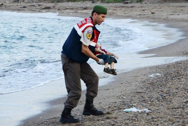 A Turkish gendarmerie carries a young migrant, who drowned in a failed attempt to sail to the Greek island of Kos, in the coastal town of Bodrum, Turkey. (Reuters Photo)