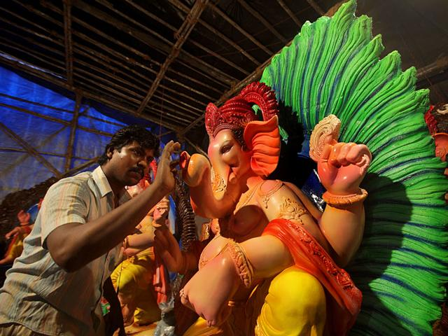 An artisan giving finishing touches to a Ganesh idol at a workshop in Lalbaug. (Kalpak Pathak/HT photo)