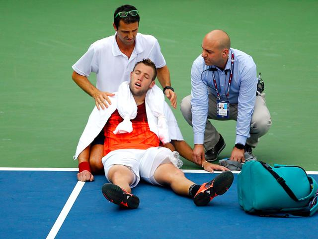 Jack Sock receives assistance from trainer Hugo Gravil for heat exhaustion during his 2015 US Open match in New York City On September 03. (AFP Photo)