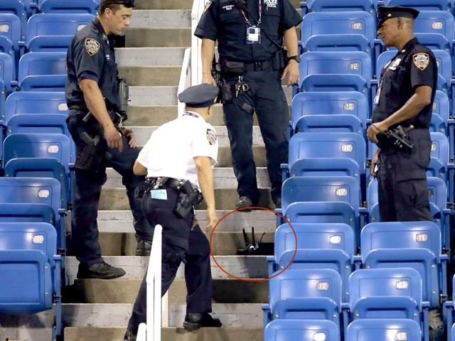 Police stand guard next to a drone (circled) after it crashed into the stands in Louis Armstrong Stadium during a 2015 US Open match in New York City. (AFP Photo)