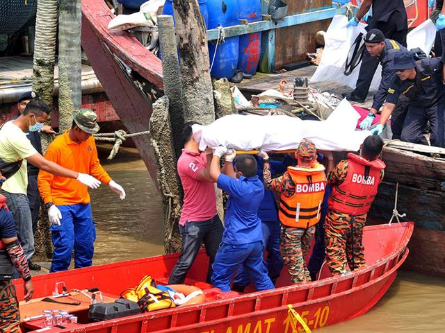 Rescuers carry a body recovered from a capsized boat believed to be carrying illegal migrants, at a jetty in Hutan Melintang, Malaysia. (Reuters Photo/ The New Straits Times)